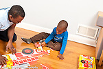 3 year old boy at home with father working together on cardboard floor puzzle showing fire truck