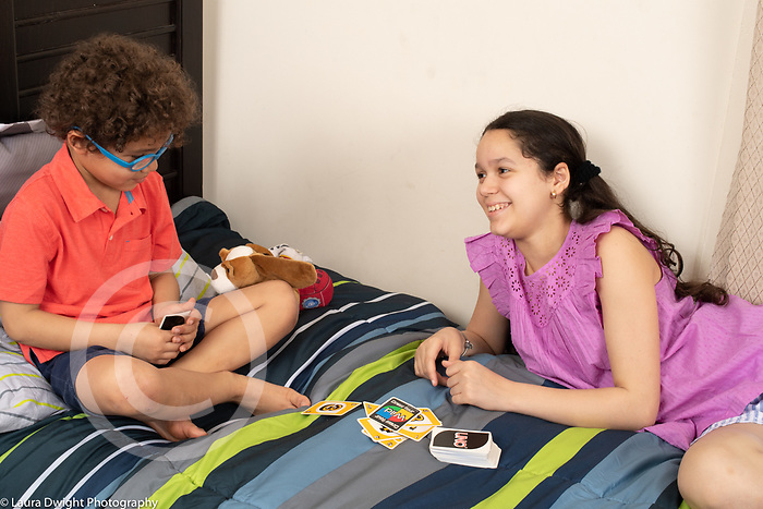 6 year old boy playing Uno card game with his 11 year old sister on bed in bedroom
