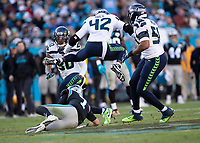 CHARLOTTE, NC - DECEMBER 15: Lano Hill #42 of the Seattle Seahawks jumps over Kyle Allen #7 of the Carolina Panthers who slides at the end of his run during a game between Seattle Seahawks and Carolina Panthers at Bank of America Stadium on December 15, 2019 in Charlotte, North Carolina.