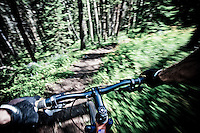 Unusual fisheye point of view POV shot of male mountain biker speeding  through a green field.  Pearl lake State Park, Craig, Colorado