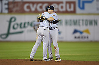 Charleston RiverDogs second baseman Oliver Dunn (right) gets a hug from shortstop Oswald Peraza (left) following their win over the Hickory Crawdads at L.P. Frans Stadium on August 10, 2019 in Hickory, North Carolina. The RiverDogs defeated the Crawdads 10-9. (Brian Westerholt/Four Seam Images)