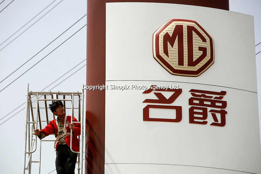 A Chinese worker stands on a platform next to a sign displaying a MG logo at the launching ceremony of the first Chinese built MG vehicles in Nanjing, China. The Chinese company is now in a position to take on Rover's assets and plan its future. It intended to relocate the engine plant and some car production plant to China but to retain some car production plant in the UK..27 Mar 2007