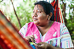 "Middle-aged Wayuu indigenous woman knitting in a ""chinchorro"" or Colombian hammock.   Knitting, crocheting and weaving are fundamental to the social and economic lives of Wayuu women in La Guajira, Colombia."