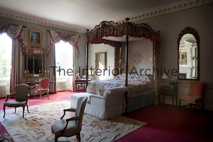 A spacious bedroom furnished with a four-poster bed with elaborate fretwork decoration on the pelmet