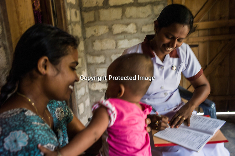 Mathumita (right) fills up the CHDR (Child Health Development Record) for Sugandhini (30) and her 9 month daughter, Rutsika during the field visits in Punaineeravi village in Kilinochchi in Northern Sri Lanka. Photo: Sanjit Das/Panos