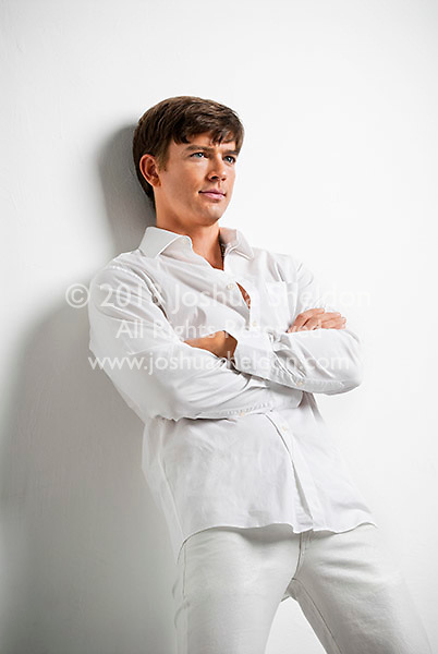 Young man leaning against white wall, arms folded