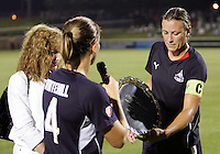 Cat Whitehill #4 of the Washington Freedom and owner Marjorie Hendricks present a plaque to Abby Wambach #20 of the Washington Freedom during a WPS match against the Boston Breakers at Maryland Soccerplex on July 29, in Boyds, Maryland.Freedom won 1-0.
