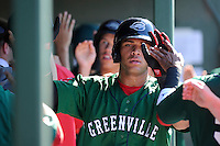 Second baseman Yoan Moncada of the Greenville Drive is congratulated after scoring a run in a game against the Charleston RiverDogs on Sunday, June 28, 2015, at Fluor Field at the West End in Greenville, South Carolina. The Cuban-born 19-year-old Red Sox signee has been ranked the No. 1 international prospect in baseball by Baseball America. Charleston won, 12-9. (Tom Priddy/Four Seam Images)