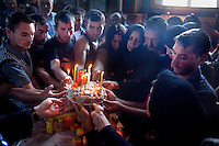 Friends and family hold up a Koliva, a traditional cake for the dead, in the church of Buzescu. The ritual was for Florea Radu, who was electrocuted while striping copper from power lines in Spain. Buzescu is known for it's ultra-wealthy Roma and their bizarre mansions that line the main street. The Roma of Buzescu are part of the Kalderash clan and are known for being coppersmiths and dealing with metal scraps. After the fall of the communist regime in the late 80's, they stripped old factories of their metals and some made a small fortune re-selling them. They are also known for making cazane, copper stills that produce alcohol such as palinka, a plum brandy.