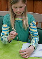 Kinder basteln ein Fensterbild mit Blüten, Mädchen zieht Schnur durch das Loch in den Ecken des Pergamentpapiers