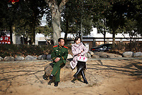 CHINA. Jiangxi Province. Jiujiang. A soldier and a woman sitting in a park. Jiujiang is a city of 4.6 million people, located on the southern shore of the Yangtze River.  2008