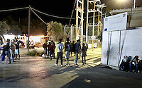 """Pictured: Migrants that have fled the fire at Moria camp gather outside its gates on Lesbos island.<br /> Re: Up to 4,000 migrants were evacuated from the Moria camp on the Greek island of Lesbos after a large fire destroyed tents and prefabricated homes.<br /> No injuries have been reported, and some migrants have now been allowed to return to the camp.<br /> Police are investigating whether the fire was deliberate, but an aid worker said it started after a food dispute.<br /> There are some 5,600 refugees currently in Lesbos, according to the UN, but the island only has capacity for 3,600.<br /> The fire destroyed 30% of the camp, according to Aris Vlashopoulos, an aid worker with the Swiss charity SAO.<br /> """"People are returning to the camp now as I can see. But the biggest number of the refugees are already on the streets, sleeping outside,"""" he added."""