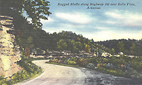 """Courtesy Bella Vista Historical Museum This postcard shows the old Highway 100 (renamed Highway 71 in 1960) going south in what is now the northern part of Bella Vista. The heading at the top of the card says """"near"""" Bella Vista because at the time, Bella Vista consisted just of the summer resort around Lake Bella Vista, several miles further south. The small house on the right stood near today's intersection of Wellington Road and 71.The old highway went under the bluffs that are visible just north of that intersection. Little Sugar Creek ran close to the highway at the time, but it was rechanneled in 1975 in preparation for the widening of Highway 71 to four lanes, completed in 1978. This card was postmarked July 20, 1954, and sent to Mrs. Futrell in Lamesa,Texas.The message reads, """"Dear Mama and Dad, We are having a nice time in Ark. Shirley thinks she'll like school fine.   We will be home in the latter part of the week, I think. Love, Irene."""""""