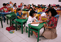 In a kindergarten class of Karya Iman School in Lippo City, Indonesia, Ms. Dwi Astuti helps a young student out with her class work. Placing an emphasis on individual performance, class size is kept small for a better student-teacher ratio. students s, te