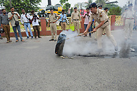Pictured: A police personal is trying to control the fire in a tyre during the protest of the congress activist , as they are protestting against the price hike in oil, gas and other daily cocmmodities in India under the rule of BJP government .Pix By-Abhisek Saha,Re: Activists of the Congress political party clash with police in protest against price rises in oil, gas and other daily commmodities by BJP government in Agartala, in the Tripura area of India. Monday 10 September 2018