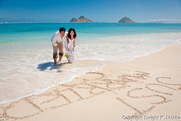 """Asian bride and groom watch a wave erase their """"Just Married"""" mark in the sand during a stroll on Lanikai beach."""