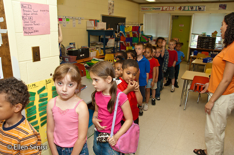 MR / Schenectady, New York. Elmer Avenue School (urban public elementary school). Kindergarten classroom. Students line up for lunch. Their teacher (Jamaican-American, West-Indian American / Caucasian) is at right. Student with pink bag (girl, age 6, type one diabetes) has her insulin pump is in the pouch on her stomach. MR: Gil11, Cul1. ID: AH-gKg. ©Ellen B. Senisi