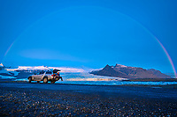 Woman sitting on a tailgate of 4x4 car with glaciers and rainbows in the background, Iceland