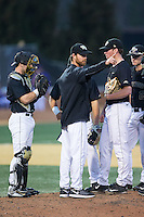 Wake Forest Demon Deacons assistant coach Matt Hobbs (31) makes a call for a relief pitcher during the game against the Clemson Tigers at David F. Couch Ballpark on March 12, 2016 in Winston-Salem, North Carolina.  The Tigers defeated the Demon Deacons 6-5.  (Brian Westerholt/Four Seam Images)