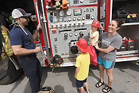 """TRUCK INSPECTION<br />Clint Bush with the Centerton Fire Department shows Aiden Slavik, 7, (from left), Everett Slavik, 2 and their mom, Anna Slavik of Centerton a department fire truck on Saturday June 5 2021 during a """"Touch a Truck"""" event at Centerton City Hall. Northwest Health, along with Centerton police and fire departments hosted the hands-on event. Kids got to sit inside a fire truck, police car and ambulance at the event. Air Evac Lifeteam landed a helicopter at the event for people to see. Go to nwaonline.com/210606Daily/ to see more photos. <br />(NWA Democrat-Gazette/Flip Putthoff)"""