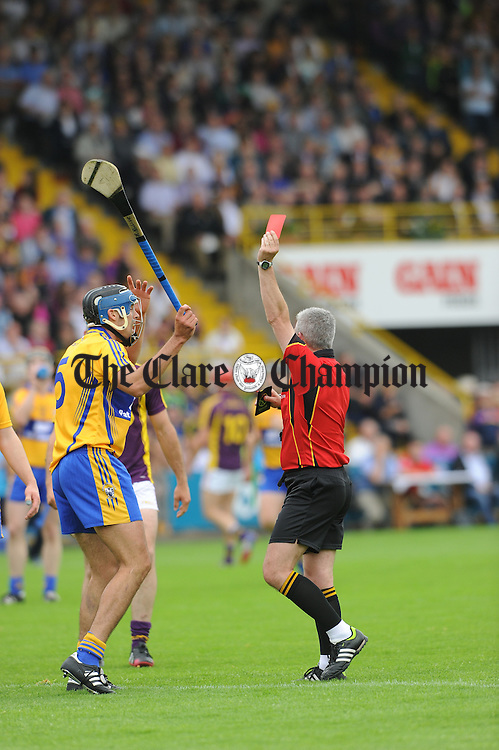 Clare's Brendan Bugler is sent off by referee John Ryan of Tipperary during their All-Ireland qualifier replay at Wexford Park. Photograph by John Kelly.