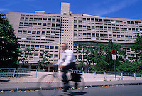 Cyclist passing the Cite Radieuse, a modernist residential housing complex designed by Le Corbusier, in Marseille, France.