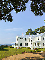 Exterior of a white, clapboard house set on the waterfront.