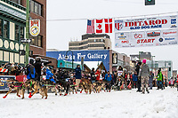 Lance Mackey  and team leave the ceremonial start line with an Iditarider and handler at 4th Avenue and D street in downtown Anchorage, Alaska on Saturday March 7th during the 2020 Iditarod race. Photo copyright by Cathy Hart Photography.com