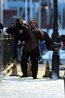 Pictured: Elijah Wood is lifted by Celyn Jones while rehearsing a scene. Tuesday 11 February 2014<br /> Re: A Swansea street was transformed into 1950s New York for new Dylan Thomas biopic 'Set Fire to the Stars' starring Holywood actor Elijah Wood.<br /> Gloucester Place in Swansea Marina was used to film a snowy scene in New York.<br /> Half a dozen 50s American cars were used for the scene played by Elijah Wood and Celyn Jones.<br /> The new movie will explore the fractious relationship between Dylan Thomas played by Jones and John Malcolm Brinnin played by WOod, who brought the Welshman to the USA and acted as his tour agent.