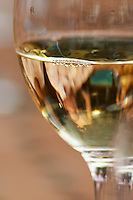 A glass of white chateauneuf, with some bubbles on the surface and lunch guests vaguely reflected in the wine. The restaurant Le Verger de Papes in Chateauneuf-du-Pape Vaucluse, Provence, France, Europe