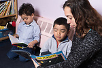 Education Preschool childcare 3-4 year olds SEIT working with boy in classroom, looking at book about planets