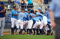 Charlotte Stone Crabs designated hitter Jace Conrad (23) is mobbed by teammates including Isaac Gil (13), Braxton Lee (30), Granden Goetzman (6), Andrew Velazquez (1) and Willy Adames (2) after a walk off base hit during a game against the Dunedin Blue Jays on July 26, 2015 at Charlotte Sports Park in Port Charlotte, Florida.  Charlotte defeated Dunedin 2-1 in ten innings.  (Mike Janes/Four Seam Images)