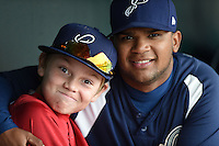 Pensacola Blue Wahoos catcher Rossmel Perez (14) in the dugout with Cincinnati Reds minor league hitting coordinator Ryan Jackson's son making a face during a game against the Jacksonville Suns on April 20, 2014 at Bragan Field in Jacksonville, Florida.  Jacksonville defeated Pensacola 5-4.  (Mike Janes/Four Seam Images)