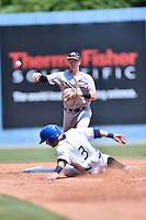 Charleston RiverDogs second baseman Kyle Holder (4) makes the turn on a double play over a hard sliding Max George (3) during a game against the Asheville Tourists at McCormick Field on July 10, 2016 in Asheville, North Carolina. The Tourists defeated the RiverDogs 4-2. (Tony Farlow/Four Seam Images)