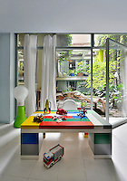 A child's play room with a colourful desk as though made from Lego bricks. A full height glass door gives access to a garden.