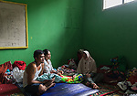 6 January 2020, Cipinas Village, Lebak Regency, Banten Province, Indonesia: 32 year olds Ana and Jamaludin (at left) with their newborn baby Sita Mustafa, who was born in an emergency shelter in Cipinas sub district,Lebak regency, Banten Province. After she fled her flood ravaged village of Cinyiru she walked many kilometres in the rain along collapsed roads and landslides before she gave birth to her baby. The flooding in and around Jakarta in recent days has killed 66 people and forced hundreds of thousands to flee with many losing everything from landslides and floods. Picture by Graham Crouch/The Australian