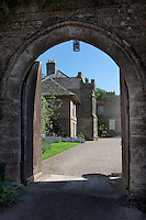 Substantial studded doors open under a pointed arch into the courtyard of Kentchurch Court, its gravel path bordered by vibrant green lawns and aromatic lavendar