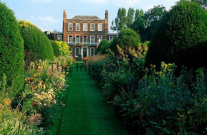 A long manicured path through the formal garden leads up to the 18th century house