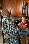 Father in kitchen with 3 year old son tasting lemon and laughing