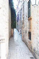 A narrow and steep backstreet cobble stone, between old houses. An old crouched lady walking with a walking stick. Dubrovnik, old city. Dalmatian Coast, Croatia, Europe.