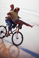 Couple riding a bike at the beach.
