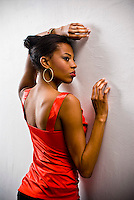 Young African American woman leaning into white wall