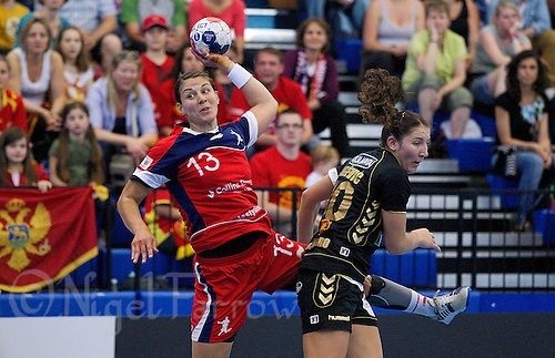 30 MAY 2012 - LONDON, GBR - Yvonne Leuthold (GBR) of Great Britain (left, in red and blue) leaps to shoot past Milena Knezevic (MNE) of Montenegro (right, in black and gold) during the women's 2012 European Handball Championship qualification match against Montenegro at the National Sports Centre in Crystal Palace, Great Britain (PHOTO (C) 2012 NIGEL FARROW)