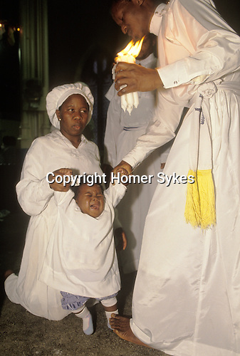 """Stratford, London. 1980's<br /> A pastor at the Celestial Church of Christ exorcises evil spirits from a disabled child.  Her concerned mother holds her hand, as the pastor stands on her foot to hold her down and at the same time pulls her upwards, to stretch her spine and free her from supernatural demons. This west African church was founded by S B J Oshoffa Mainly attended by Yoruba people from western Nigeria the church  flourishes with offshoots in London Paris and New York This  photograph is taken from the book The Storm is Passing Over"""""""