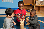 Education Preschool Headstart 3-4 year olds group of three boys building with wooden blocks together