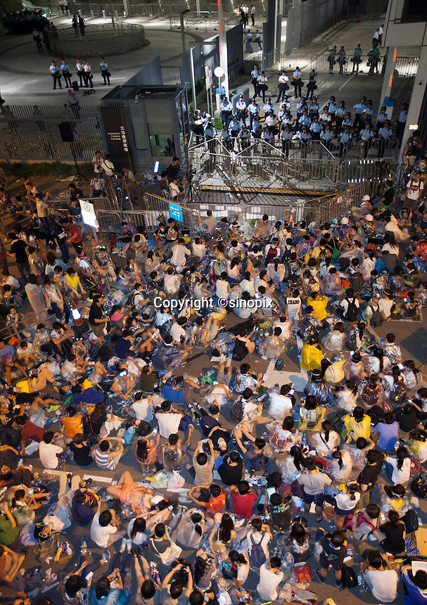 Student protestors are seen at an overnight mass sit-in in front of Hong Kong's Central government offices, Hong Kong, China, 28 September 2014. It was announced at the student protest that the society-wide mass disobedience campaign, Occupy Central would commence immediatley - three whole days earlier than was previously forecast. The students and the Occupy Central supporters are protesting the slow pace of democratic reform imposed by the Chinese government on the Hong Kong people.