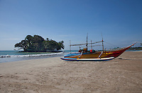 A local fishing boat is drawn up on the beach by Taprobane Island