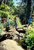 Children hiking accross stream at The Nature Center, Oahu