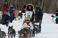 Paige Drobny and team run past spectators on the bike/ski trail near University Lake with an Iditarider in the basket and a handler during the Anchorage, Alaska ceremonial start on Saturday, March 7 during the 2020 Iditarod race. Photo © 2020 by Ed Bennett/Bennett Images LLC
