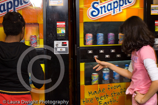 Public School elementary school lunch time cafeteria two 5th grade girls selecting drinks from vending machines horizontal